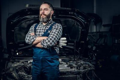 A man near the car in a garage.