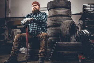A man sits on an old tire in a garage.