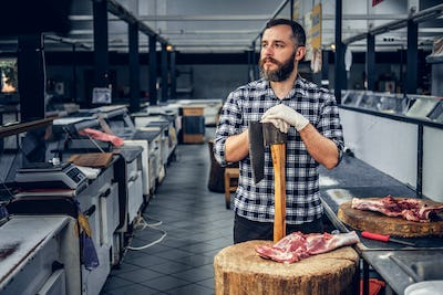 Portrait of a butcher holds an axe and fresh cut meat.