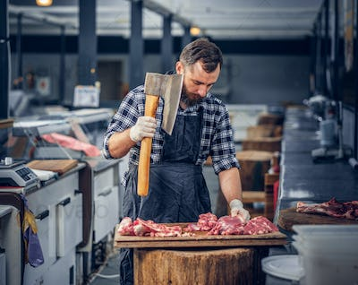 Bearded butcher cuts meat with axe.