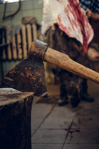 Close up image of axe over bearded butcher on background.