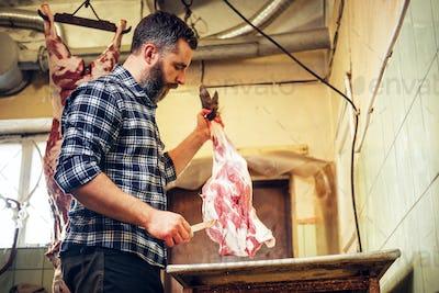 Bearded butcher cut fresh bacon meat.