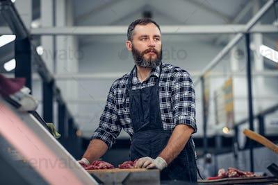 Bearded butcher serving fresh cut meat.