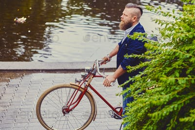 A man on a retro bicycle in a park.