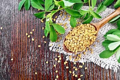 Fenugreek in spoon with leaves on board top