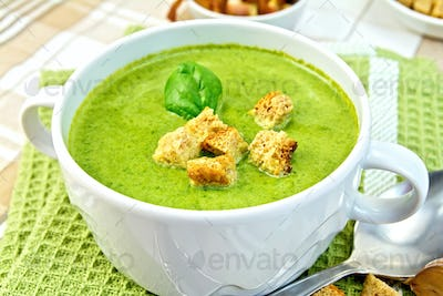 Soup puree with spinach and spoon on a napkin
