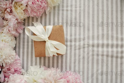 Craft gift box and peonies frame flat lay on rustic table cloth