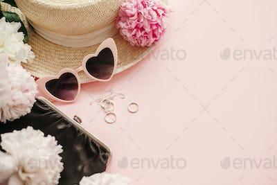 Stylish girly pink retro sunglasses,peonies, jewelry, hat, purse on pastel pink paper