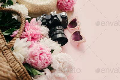 Stylish  pink peonies in straw bag, photo camera, retro sunglasses, hat on pastel pink paper
