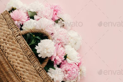 Stylish straw rustic bag with white and pink peonies on pastel pink paper