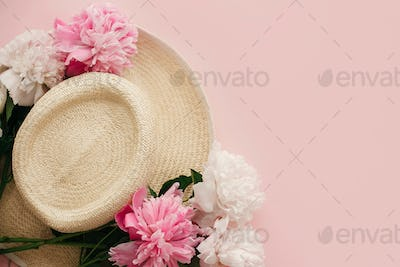 Straw hat with white and pink peonies on pastel pink paper, flat lay