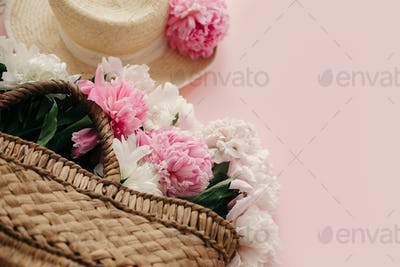 Straw hat and rustic bag with white and pink peonies on pastel pink paper
