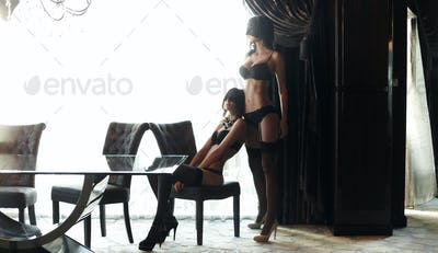 Two hot women in a black lingeries.