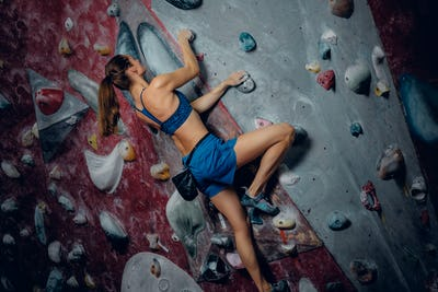 Female climber. Extreme indoor climbing.