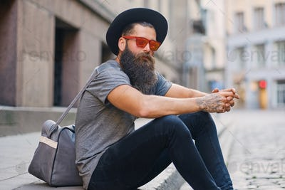 A man sits on a step on a street.