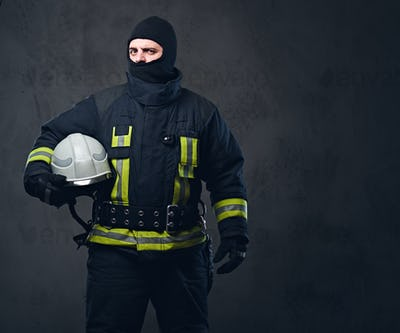 Firefighter in a uniform holds safety helmet.