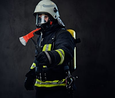 Firefighter dressed in a uniform holds a red axe.