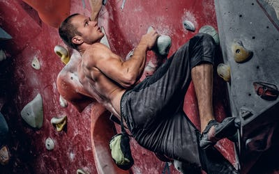Shirtless male on a climbing wall.