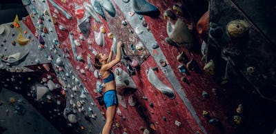 Professional female climber on a bouldering wall.