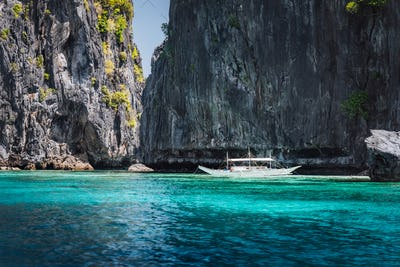 El Nido, Palawan, Philippines. Rock formation and tourism boat in ocean lagoon near entrance to