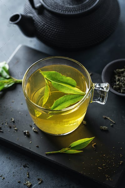 Brewed chinese green tea served in cup on table