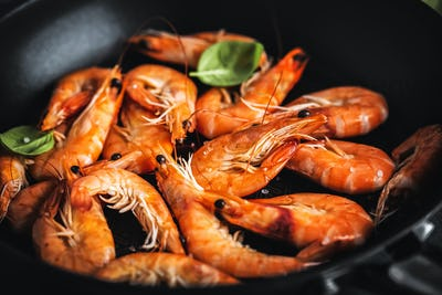 Fried shrimps with spices on pan