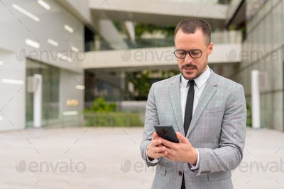Hispanic bald bearded businessman using phone with eyeglasses in the city outdoors