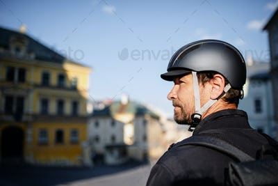 Delivery man courier with bicycle helmet in town