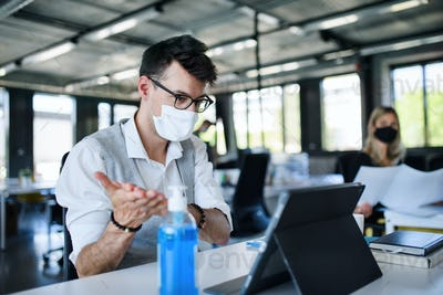 Young people with face masks back at work in office after lockdown, disinfecting hands