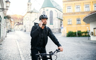 Front view of delivery man courier with bicycle in town, using smartphone