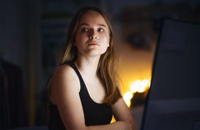 Worried young girl with computer sitting indoors, internet abuse concept