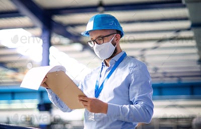 Technician or engineer with protective mask and helmet working in industrial factory