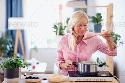 Senior woman cooking in kitchen indoors, stirring pasta in pot