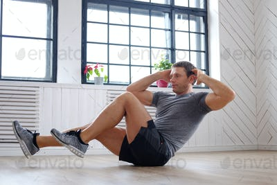 Middle age man doing stomach workouts.