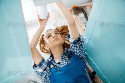 Female plumber lying on the floor, top view