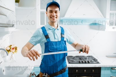 Male furniture maker holds measuring tape