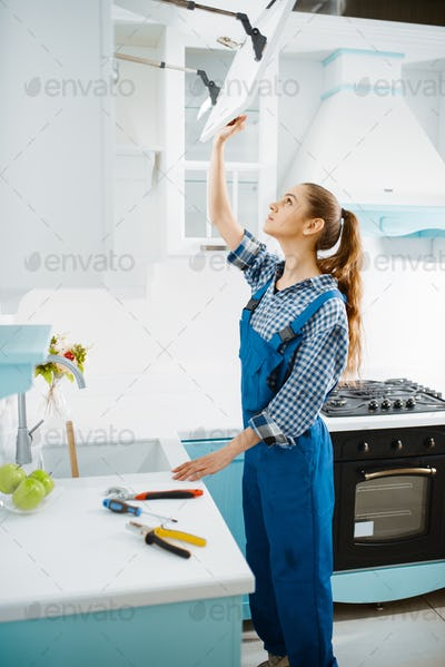 Female furniture maker in uniform repair cupboard