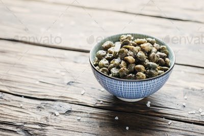 Salt capers on the wooden table