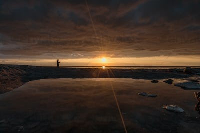 Man fishing at sunrise on the line of horizon