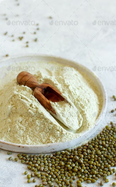 Mung beans flour and grain on a plate with a wooden spoon