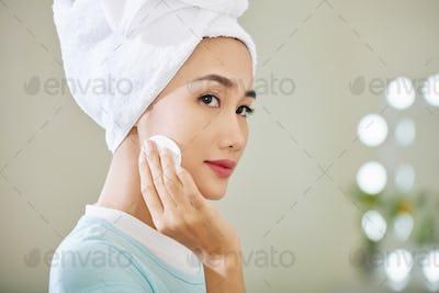 Beautiful woman applying toner