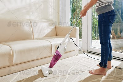 Woman vacuum cleaning living room