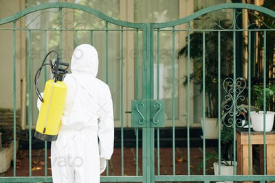 Worker disinfecting house gates