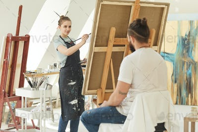Young Female Artist Painting Portrait in Studio
