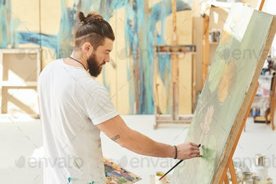 Modern Male Artist Painting Picture in Studio