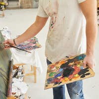 Unrecognizable Male Artist Painting Picture in Studio