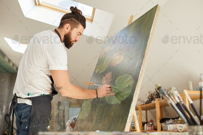 Bearded Man Painting on Easel in Studio