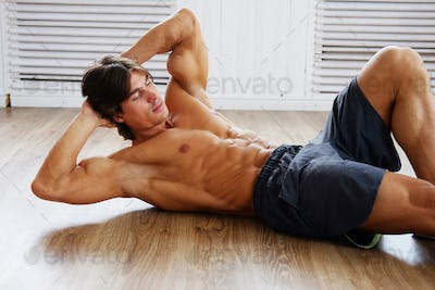Male doing stomach exercising on a floor.
