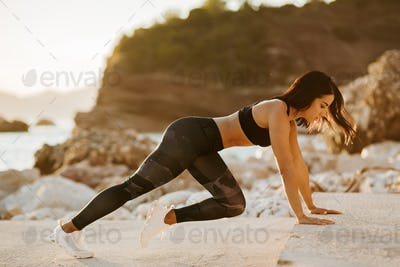 sexy athletic woman stretching exercises outdoors