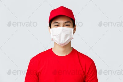Close-up portrait of cheerful asian delivery guy in medical mask and red cap uniform, t-shirt
